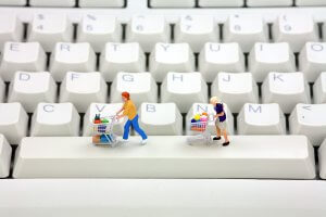 Miniature people pushing trolleys on a keyboard_Image used under license from Shutterstock